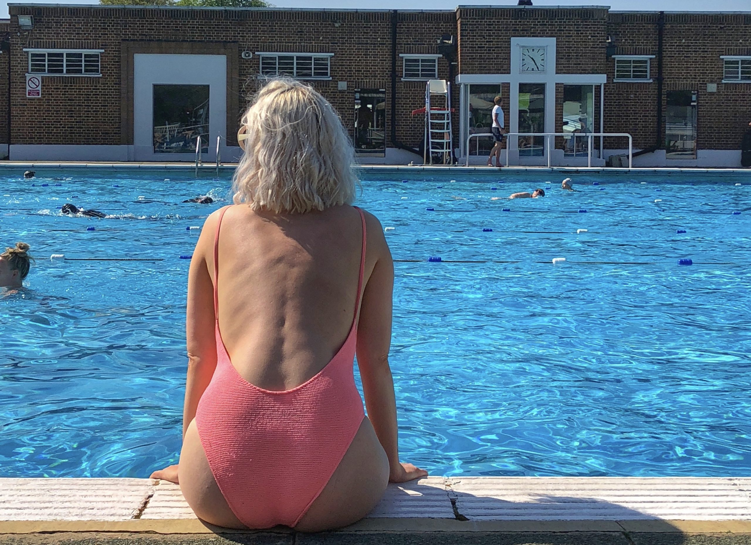 Image of Sarah sat by a swimming