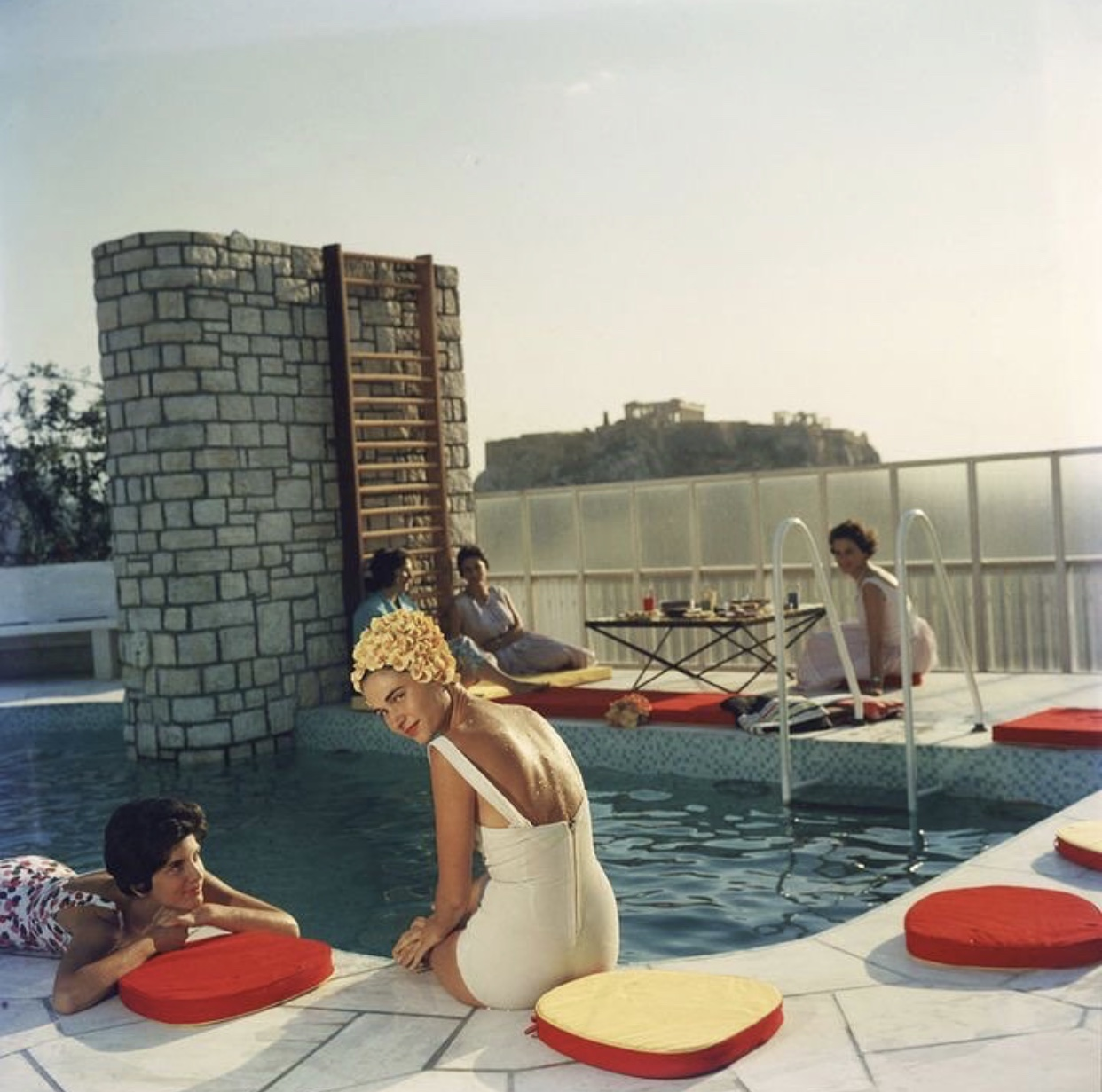 An image of women sat by pool retro style