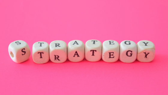Pink Image with dice spelling out the word Strategy